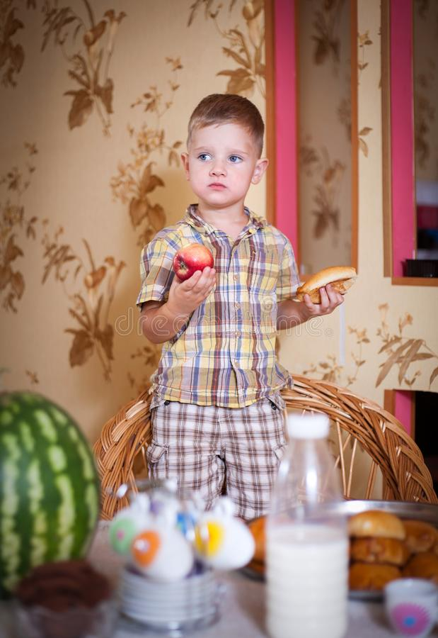 Little boy eating a pie in the kitchen. At the table. Shooting in the interior in retro style royalty free stock photos
