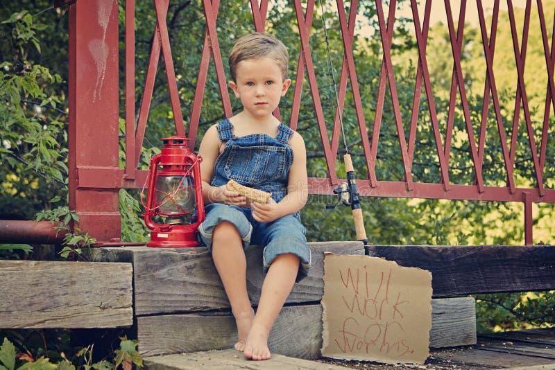Little boy eating sandwich on bridge. Little boy bridge fishing eating stock images