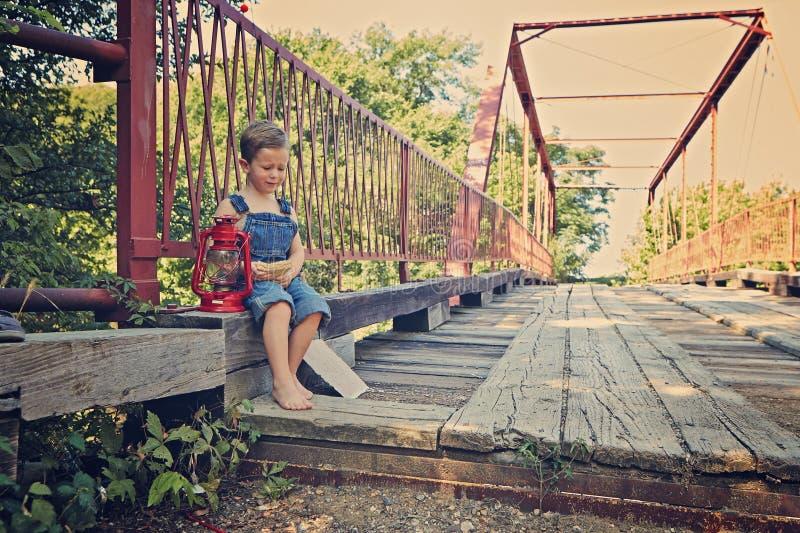 Little boy eating sandwich on bridge. Little boy bridge fishing eating royalty free stock photography