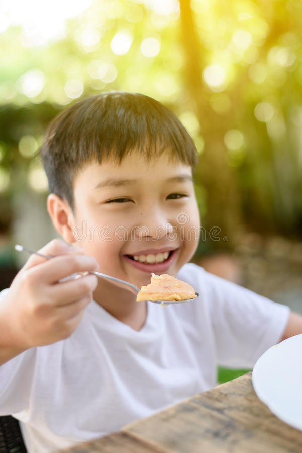 Little boy eating. Selective focus at Young Thai boy eating with food on the wooden table with his family in the garden. And out focus tree background stock photos
