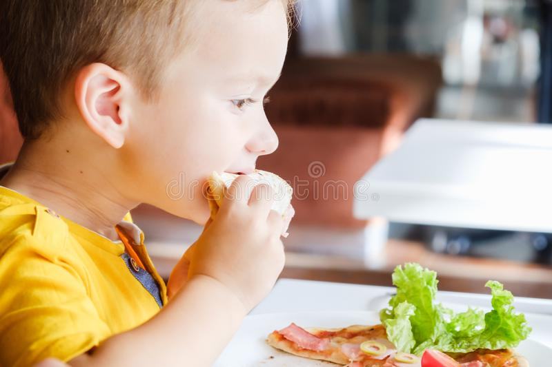 Little boy eating a small pizza stock photography