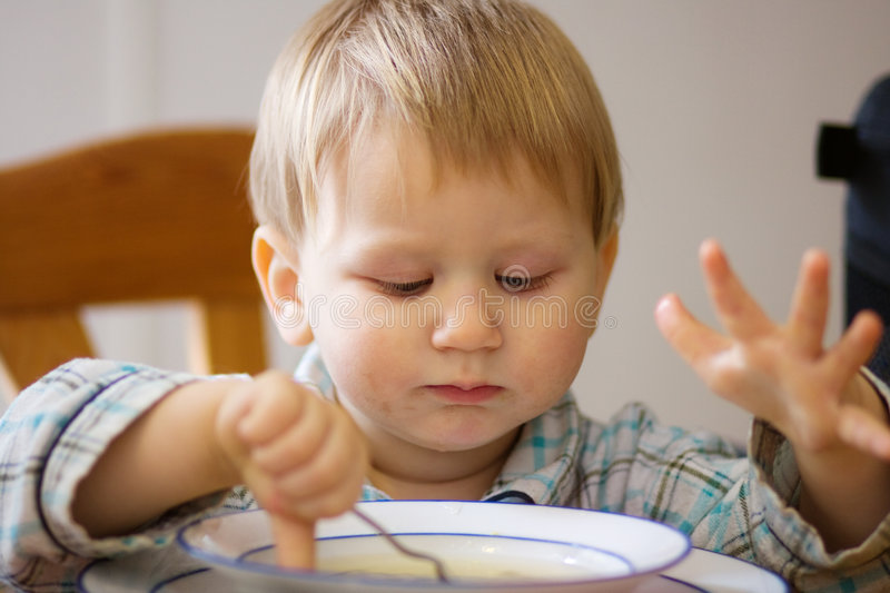 Little boy eating soup stock images