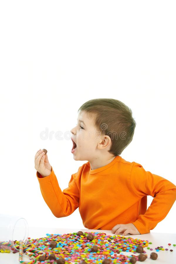 Little boy eating sweets. Happy child four years old little boy eating sweets, isolated on white background royalty free stock image