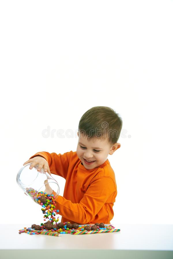 Little boy eating sweets. Happy child ( four years old little boy ) eating sweets, isolated on white background stock photo