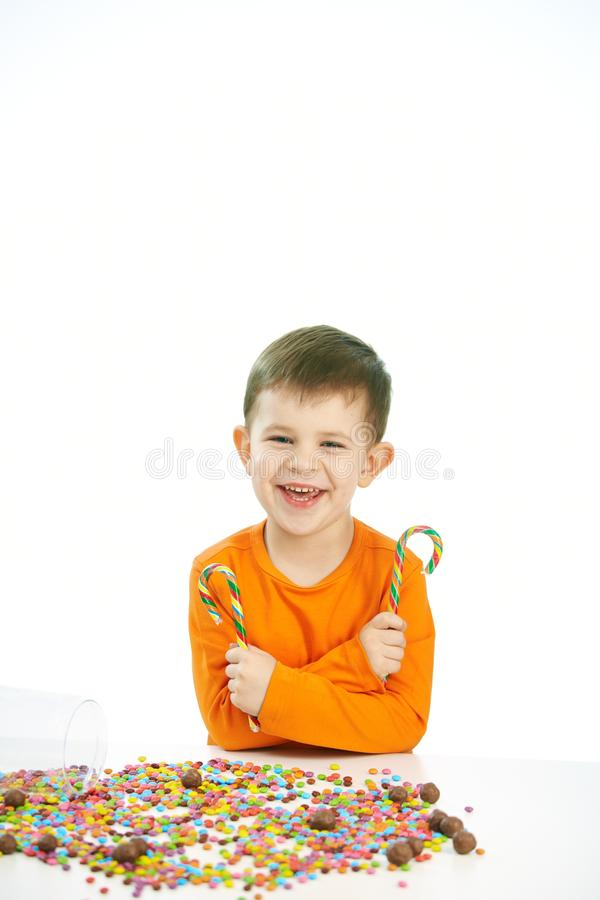 Little boy eating sweets. Happy child ( four years old little boy ) eating sweets, isolated on white background stock image