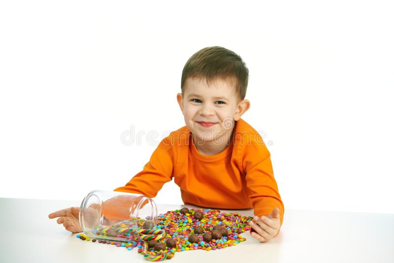 Little boy eating sweets. Happy child ( four years old little boy ) eating sweets, isolated on white background stock photos