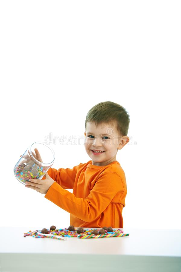 Little boy eating sweets. Happy child ( four years old little boy ) eating sweets, isolated on white background royalty free stock photos