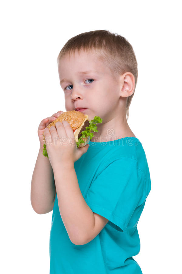 Little boy eats hamburger royalty free stock photography