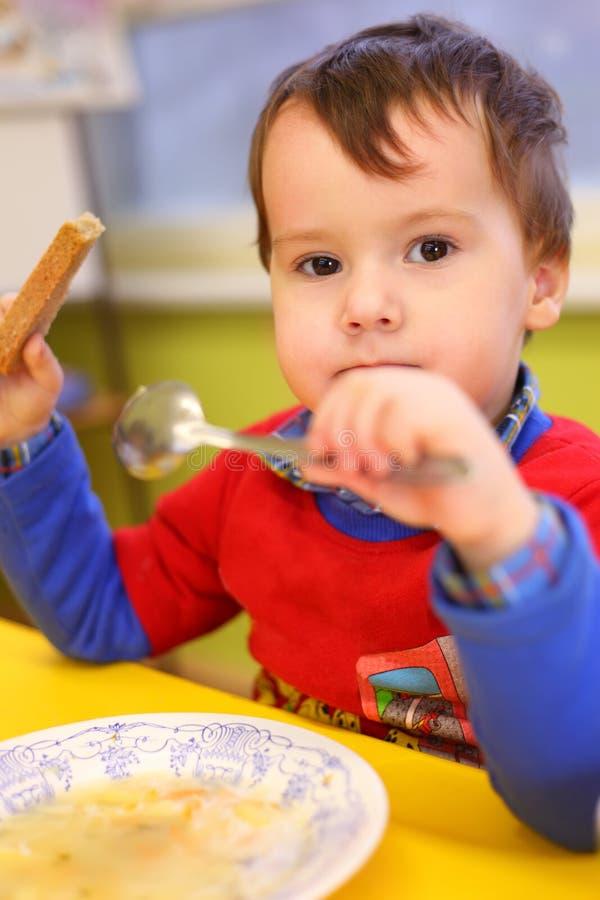 Little boy eats in kindergarten stock photos