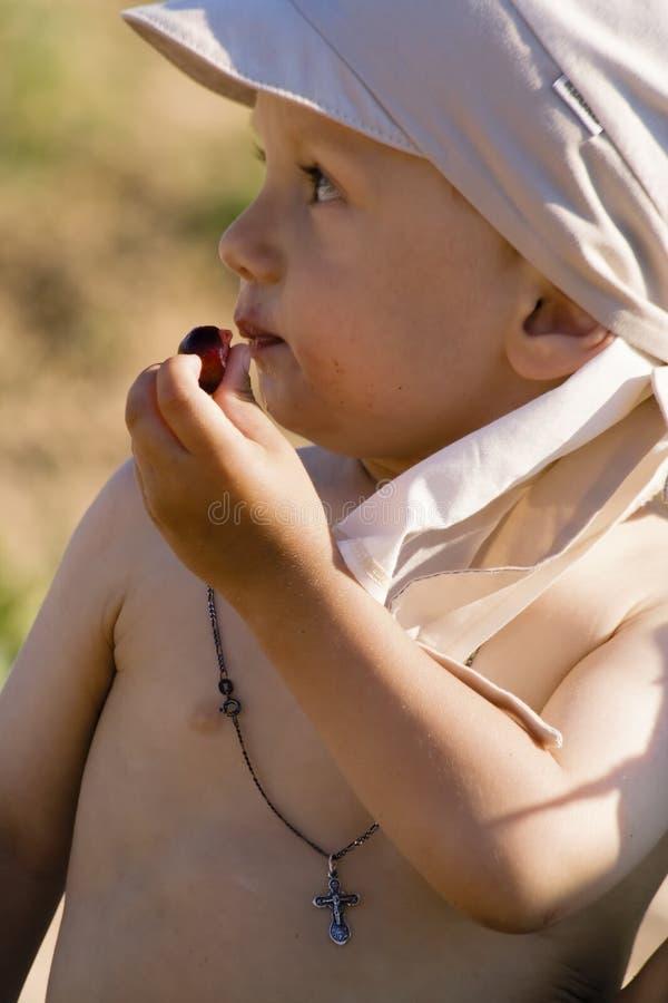 Little boy eats a ripe cherry stock image