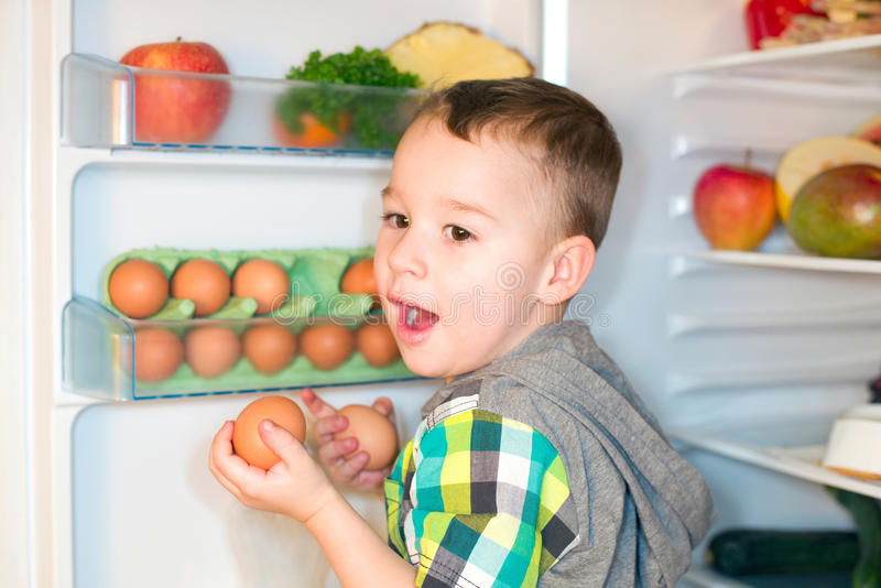 Little boy with eggs. Little boy keeps eggs from the refrigerator stock image