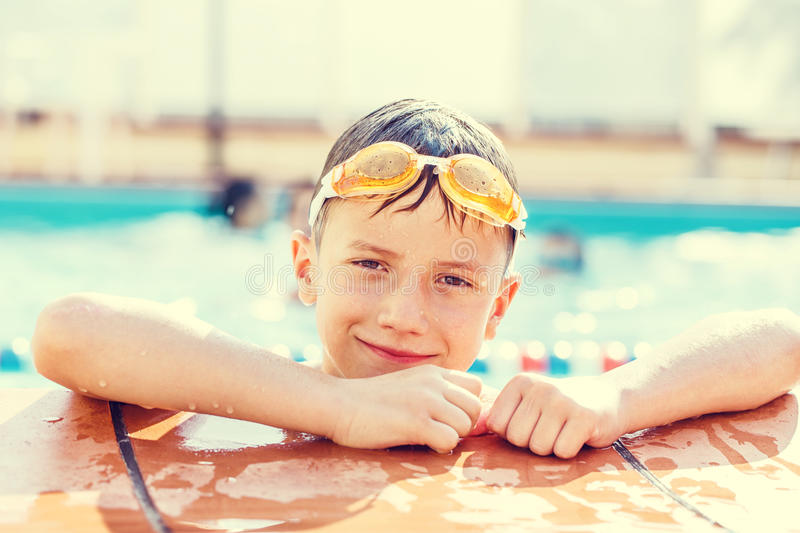 Little boy elbowing at swimming pool stock image