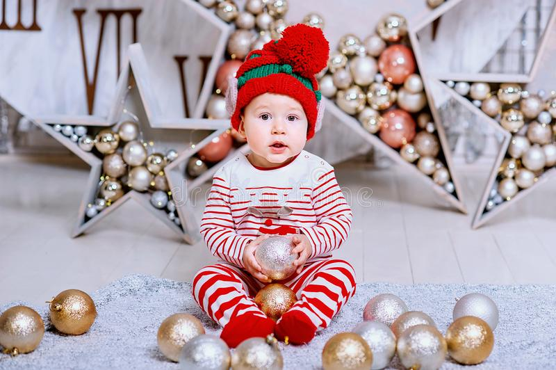 Little boy in elf hat waiting for a Christmas holding tree decoration. Merry Christmas and Happy Holiday stock photo