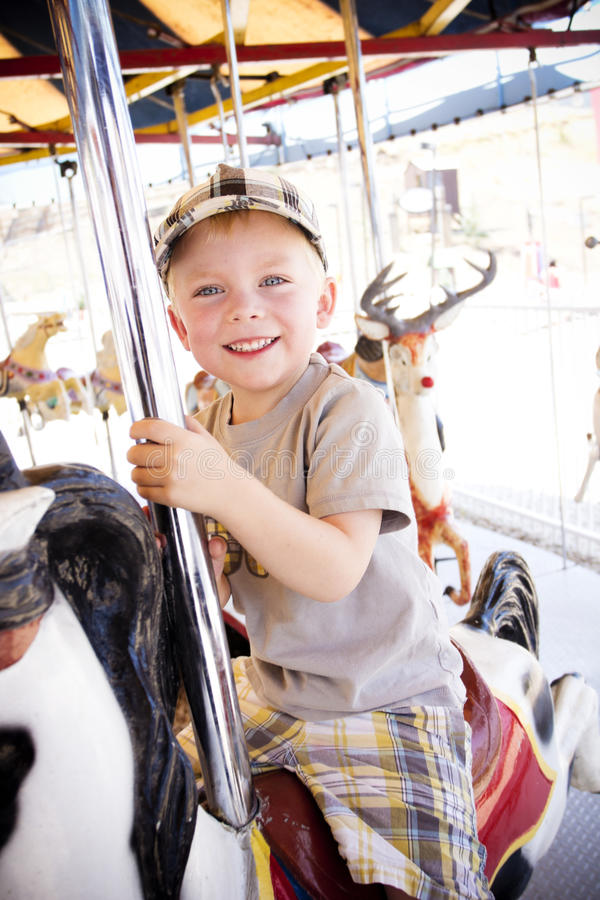 Little Boy em um carrossel do carnaval foto de stock royalty free