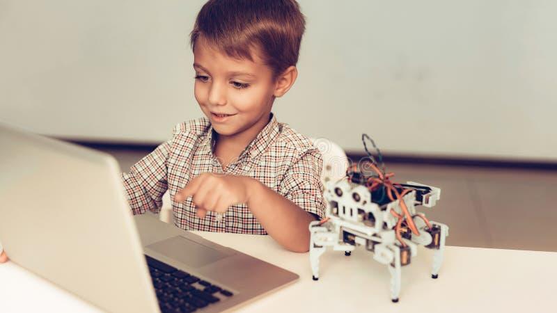 Little Boy en robot de programación de la camisa en casa fotografía de archivo