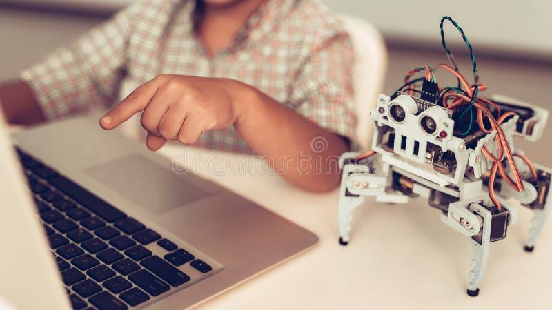 Little Boy en robot de programación de la camisa en casa foto de archivo libre de regalías