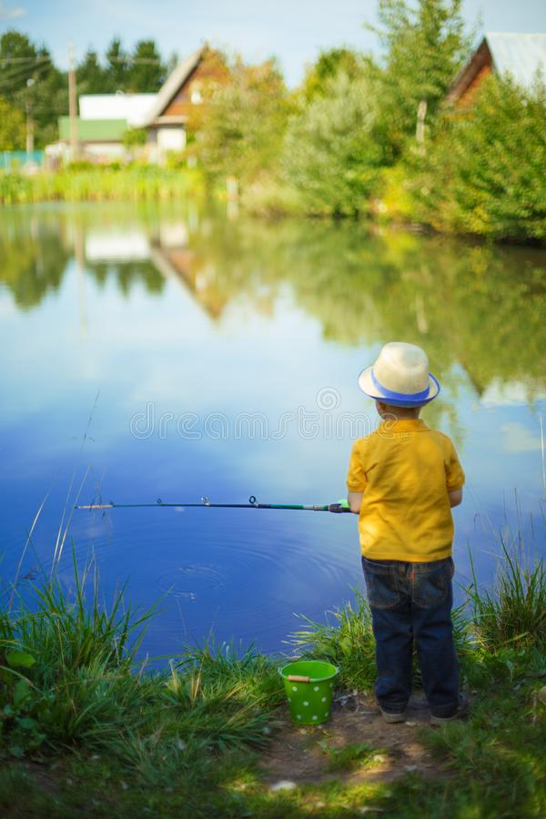 Little boy is engaged in fishing in a pond. Child with a dairy i royalty free stock photos