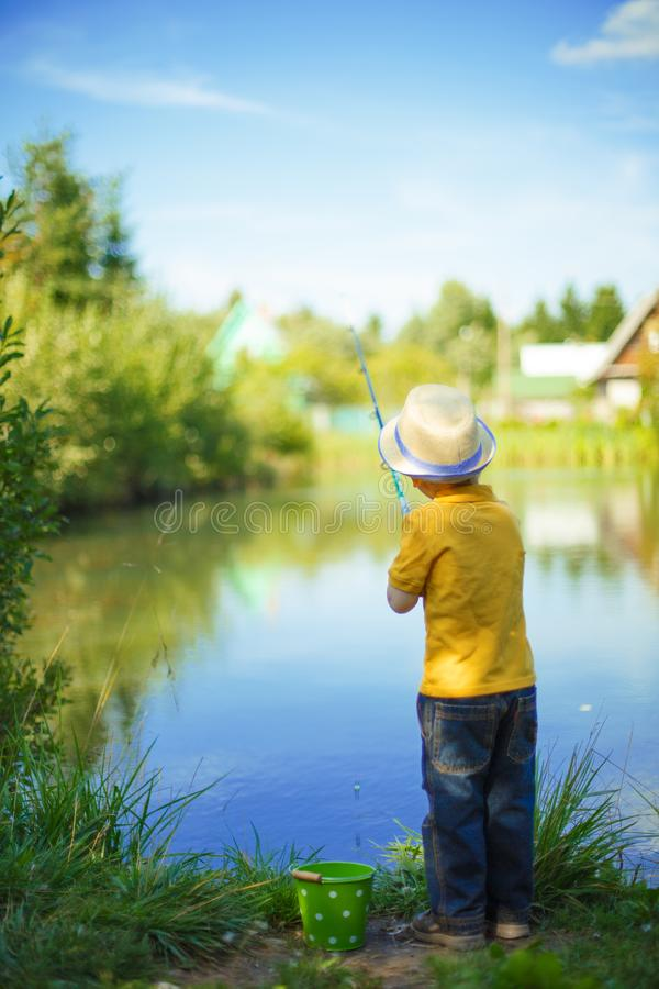 Little boy is engaged in fishing in a pond. Child with a dairy i royalty free stock images