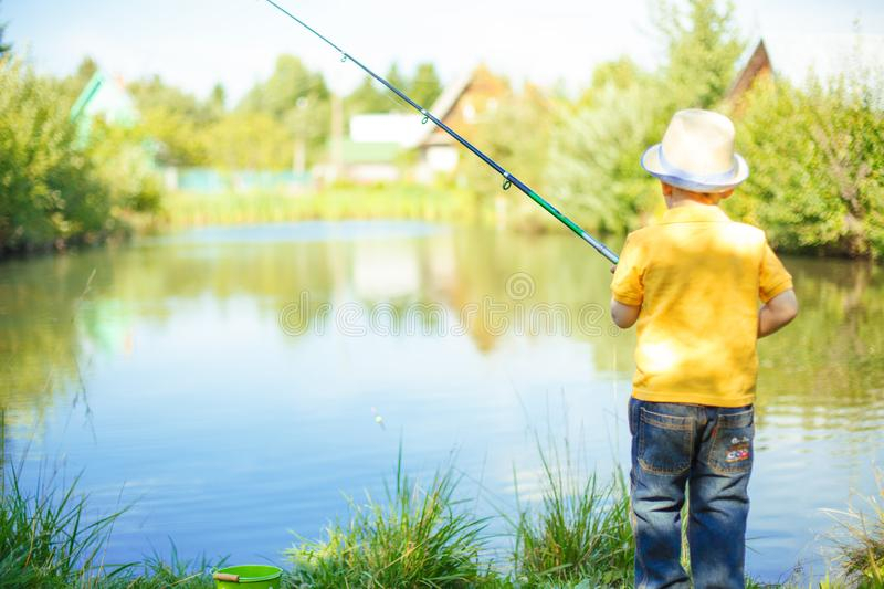 Little boy is engaged in fishing in a pond. Child with a dairy i. N his hands royalty free stock photos