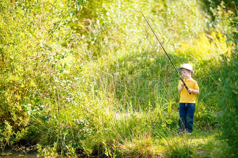 Little boy is engaged in fishing in a pond. Child with a dairy i stock images