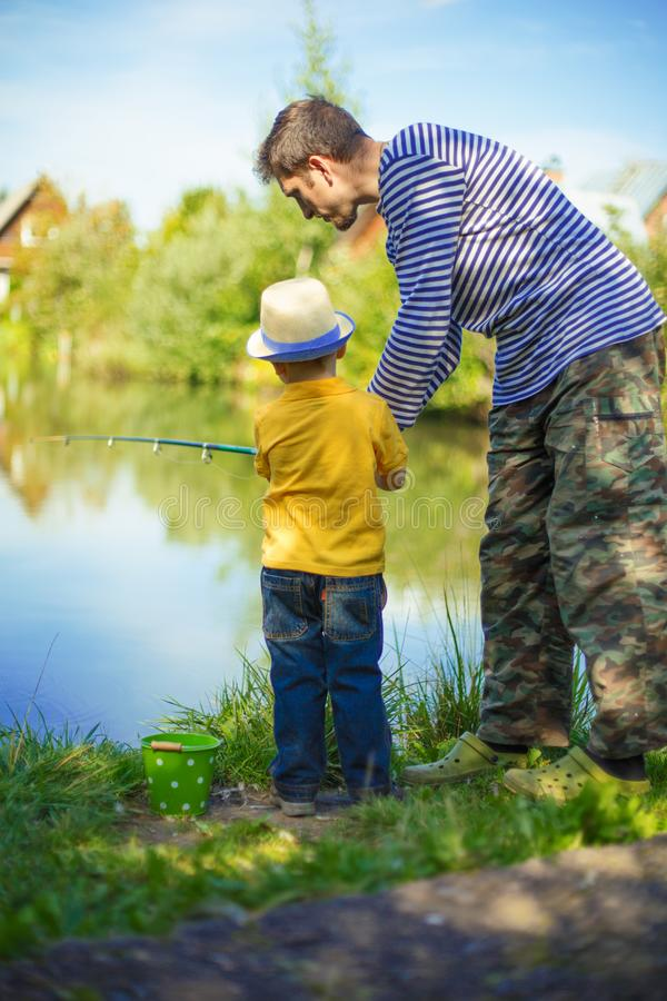 Little boy is engaged in fishing in a pond. Child with a dairy i royalty free stock photo