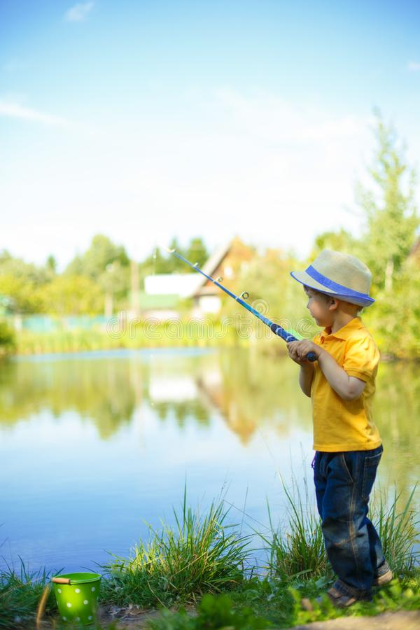 Little boy is engaged in fishing in a pond. Child with a dairy i stock image