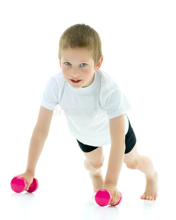 A little boy is lifting dumbbells. royalty free stock image