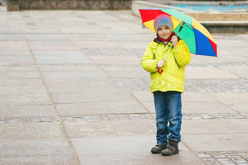 Little boy enjoying rainy weather in city street. Happy kid wuth colorful umbrella outdoors stock images