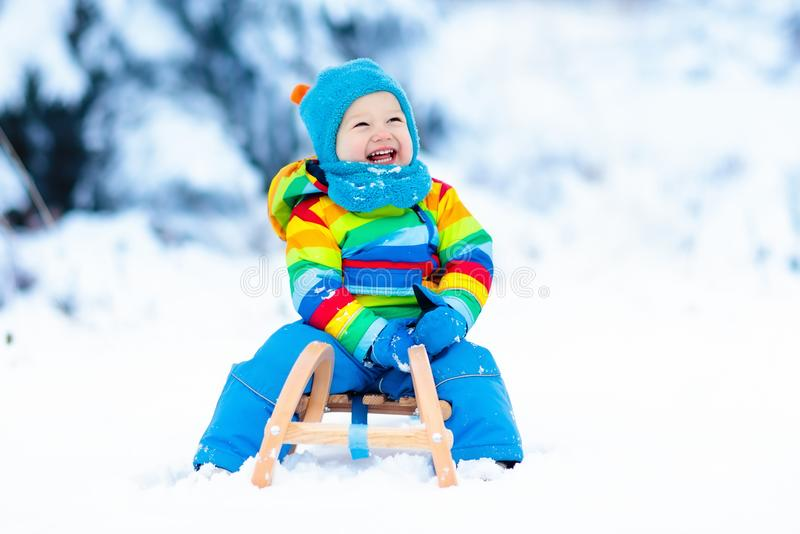 Boy on sleigh ride. Child sledding. Kid with sledge. Little boy enjoying a sleigh ride. Child sledding. Toddler kid riding a sledge. Children play outdoors in stock photos