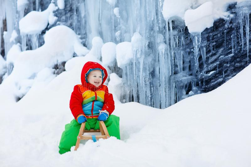 Boy on sled ride. Child sledding. Kid on sledge. Little boy enjoying a sleigh ride. Child sledding. Toddler kid riding a sledge. Children play outdoors in snow stock photos