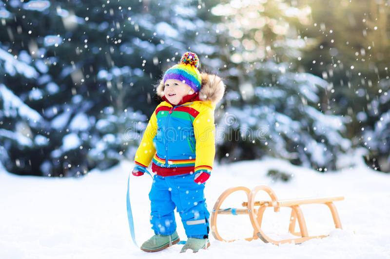 Little boy enjoying a sleigh ride. Child sledding. Toddler kid riding a sledge. Children play outdoors in snow. Kids sled in the stock photo