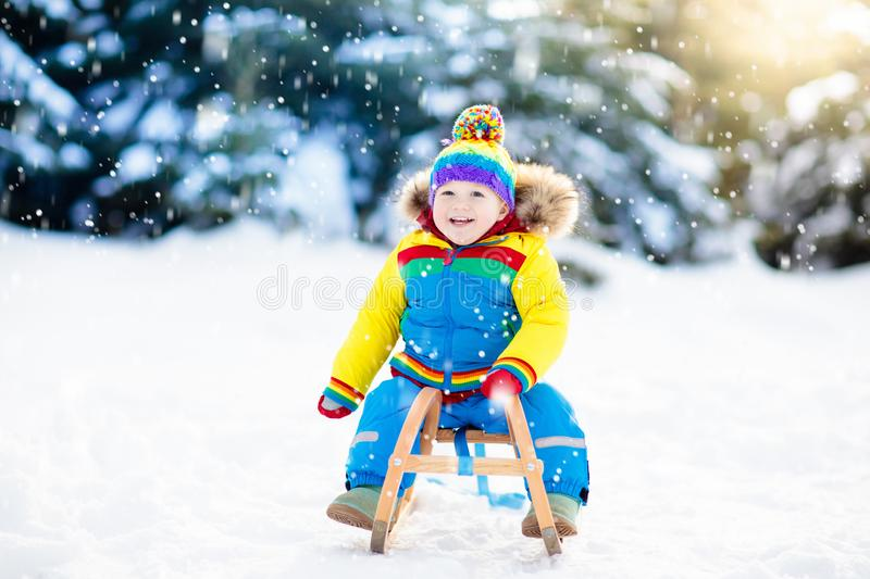 Little boy enjoying a sleigh ride. Child sledding. Toddler kid riding a sledge. Children play outdoors in snow. Kids sled in the stock images