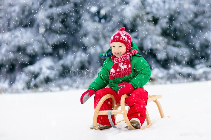 Little boy enjoying a sleigh ride. Child sledding. Toddler kid riding a sledge. Children play outdoors in snow. Kids sled in the royalty free stock photos