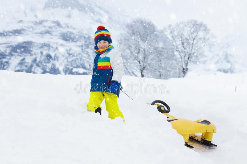 Little boy enjoying a sleigh ride. Child sledding. Toddler kid riding a sledge. Children play outdoors in snow. Kids sled in the stock image