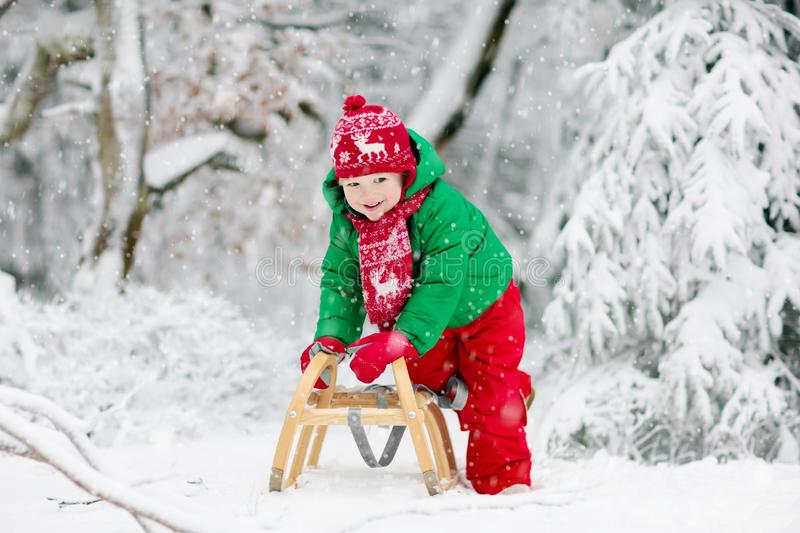 Little boy enjoying a sleigh ride. Child sledding. Toddler kid riding a sledge. Children play outdoors in snow. Kids sled in the. Alps mountains in winter royalty free stock images
