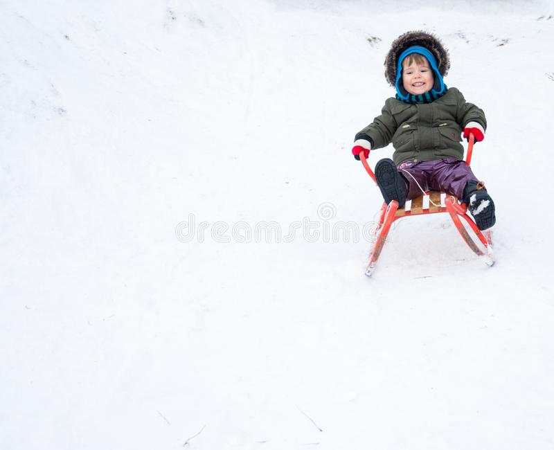 Little boy enjoying a sleigh ride. Child sledding. Toddler kid riding a sledge. stock image