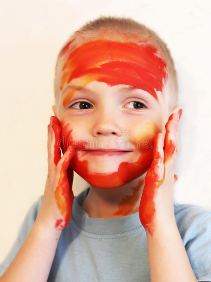 A little boy with face and hands smeared with colored paints stock photo