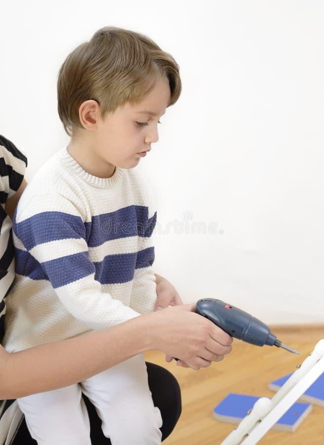 Little Boy facendo uso dello strumento diy che ? aiutato dal genitore fotografia stock