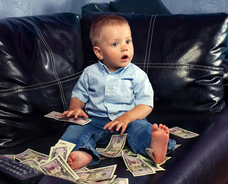 Little boy with fake money. Thinking little boy with fake money on a leather couch stock photography