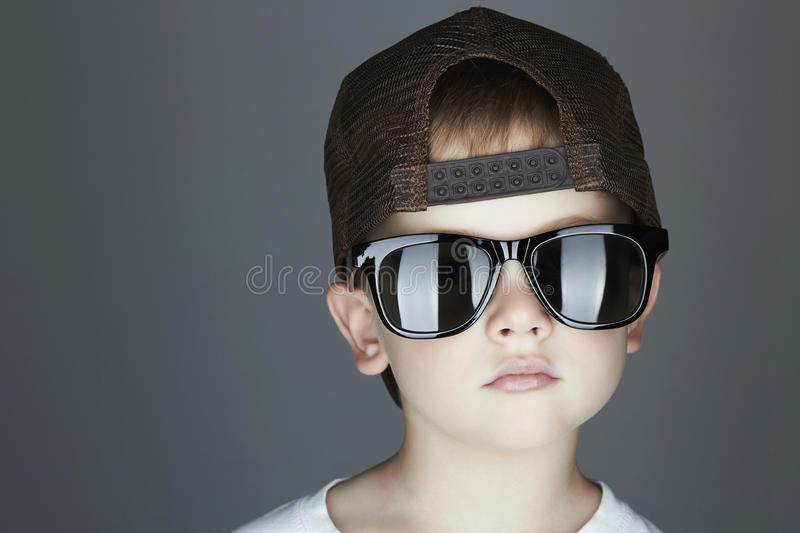 Little boy. fashion children.handsome in sunglasses and Tracker Hat. Child in Cap stock photography
