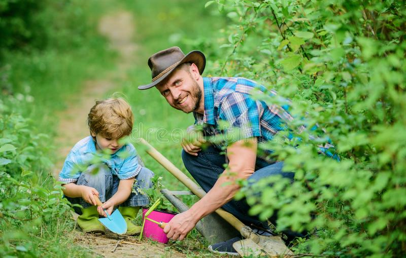 Little boy and father in nature background. Gardening tools. Gardening hobby. Dad teaching little son care plants. Spring gardening routine. Planting flowers royalty free stock photo