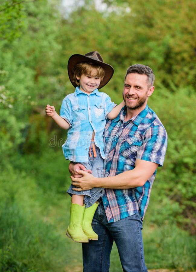 Little boy and father in nature background. Spirit of adventures. Child having fun cowboy dad. Farm family. Holidays at royalty free stock photo