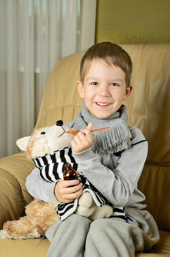 Little boy feeds medicinal syrup the toy dog and looking at came royalty free stock photos