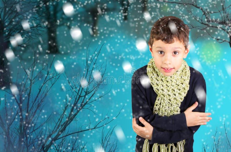 Little boy feeling cold under snow stock photos