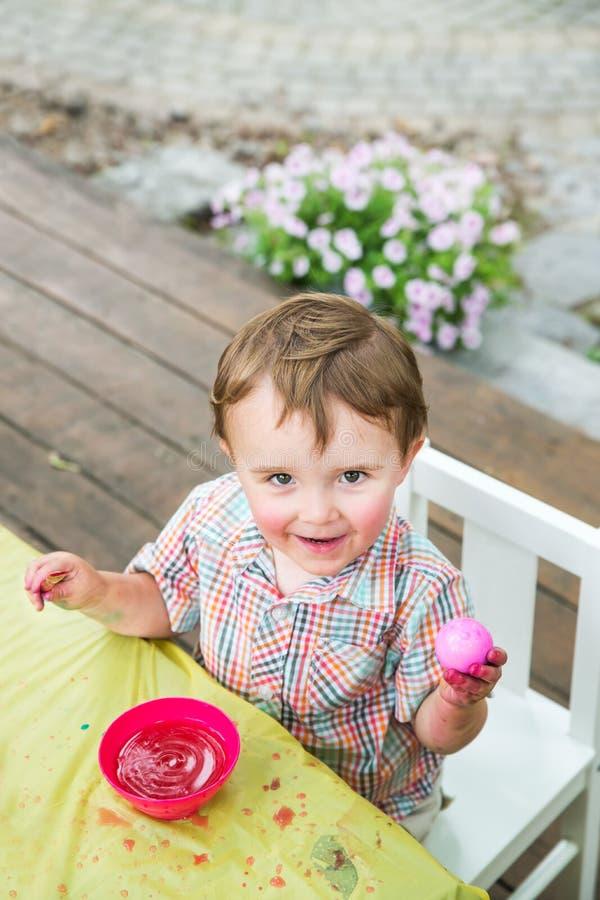 Little Boy feliz levanta com seu ovo da páscoa cor-de-rosa tingido imagem de stock