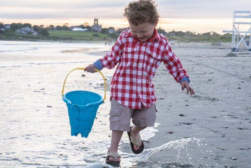 Little Boy feliz na praia com o balde azul no por do sol imagem de stock