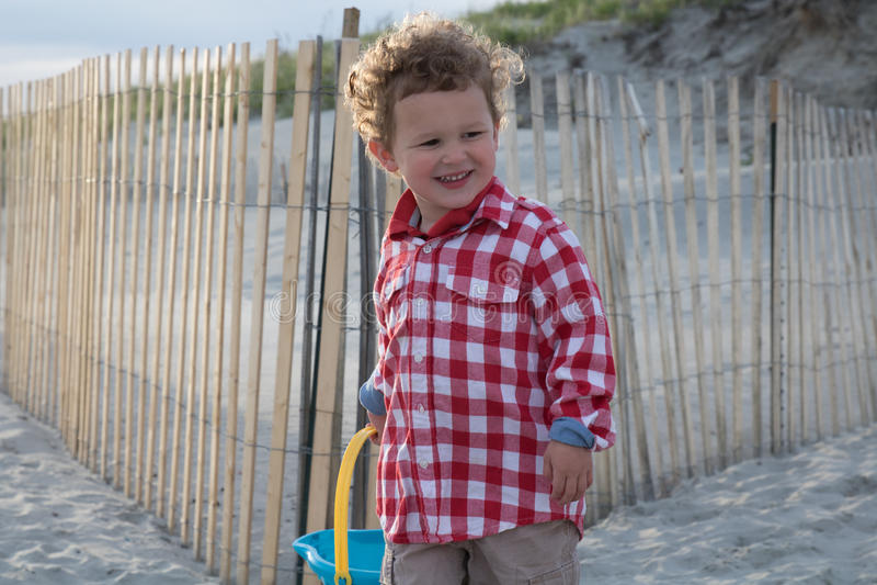 Little Boy feliz na praia com o balde azul no por do sol imagens de stock royalty free