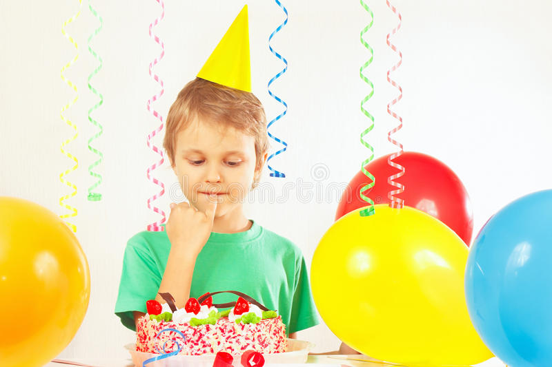 Little boy in festive hat looking at birthday cake stock photography
