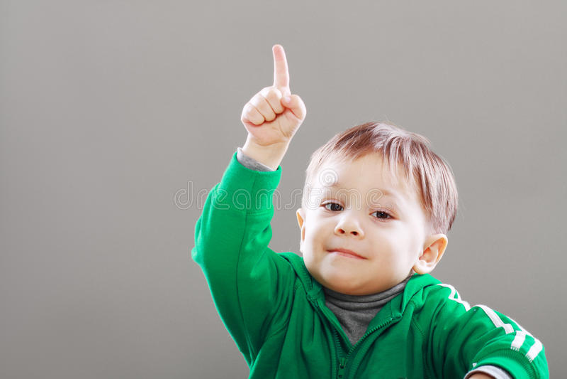 Little boy finger upward. Little boy with idea showing finger upward over grey backgound royalty free stock images