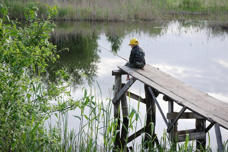 The little boy fishing on the river bank. Boy siting with sticks in hands. stock image